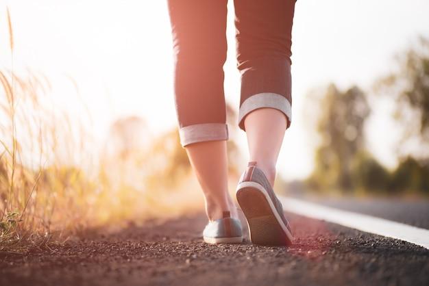 Closeup mulher caminhando em direção ao lado da estrada. conceito passo Foto Premium