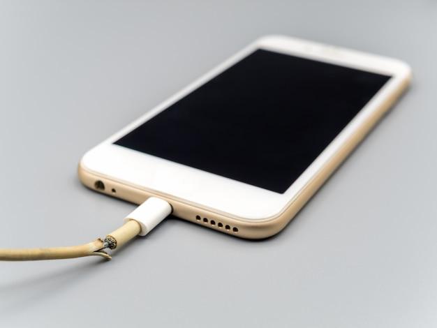 Closeup o cabo do carregador de smartphone danificado Foto Premium