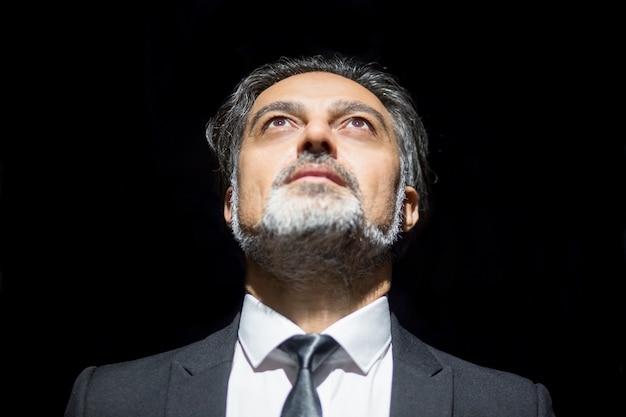 Closeup of serious business leader looking upwards Foto gratuita