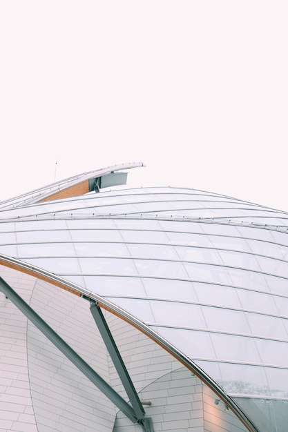Closeup olhar de um edifício moderno, com janelas de vidro branco sob um céu cinzento Foto gratuita