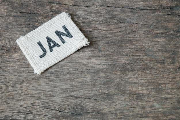 Closeup pequeno picec de calendário de tecido no mês de janeiro no fundo da mesa de madeira Foto Premium