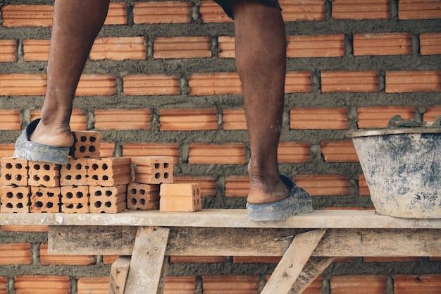 Closeup, perna, de, profissional, trabalhador construção, colocar, tijolos, em, novo, local industrial Foto Premium