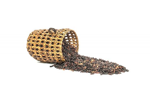 Closeup pilha de arroz preto chamado arroz riceberry com vime de madeira, arroz com altos nutrientes isolado no branco Foto Premium