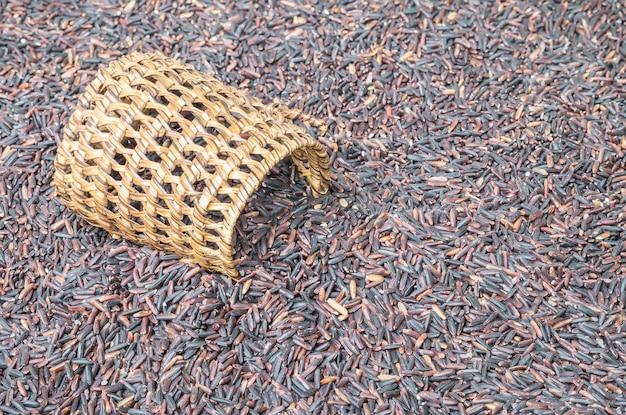 Closeup pilha de arroz preto chamado arroz riceberry com vime de madeira Foto Premium