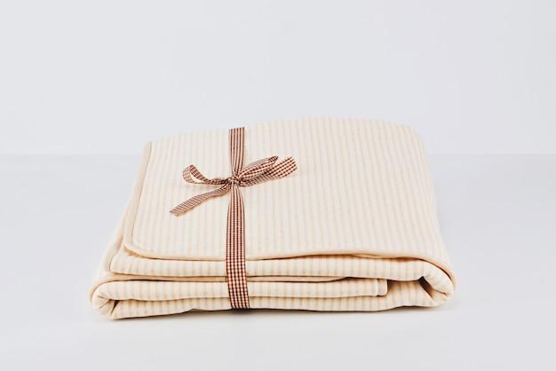 Closeup pilha embrulhado cobertor de algodão bege natural dobrado em branco Foto Premium