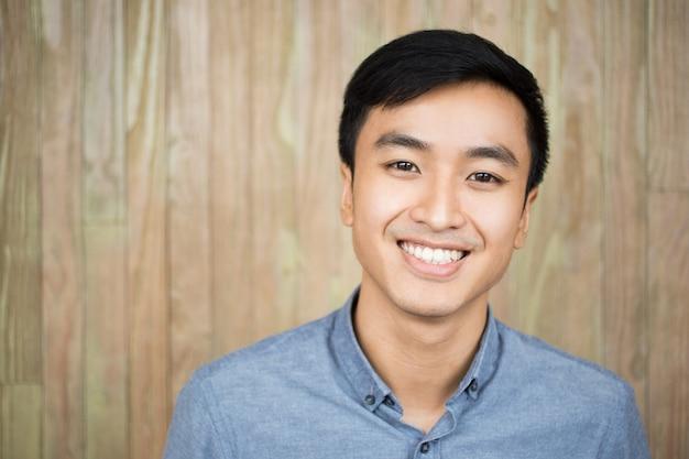 Closeup portrait of smiling handsome asian man Foto gratuita