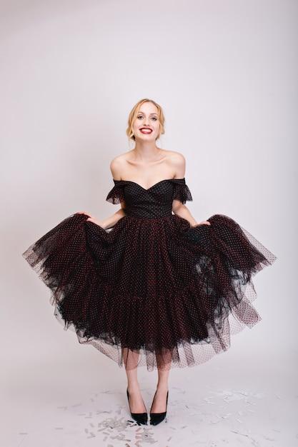 Closeup retrato da bela loira experimentando um vestido preto fofo, garota mostrando seu belo pano. ela tem cabelos presos, ombros abertos, calça sapatos pretos. isolado.. Foto gratuita