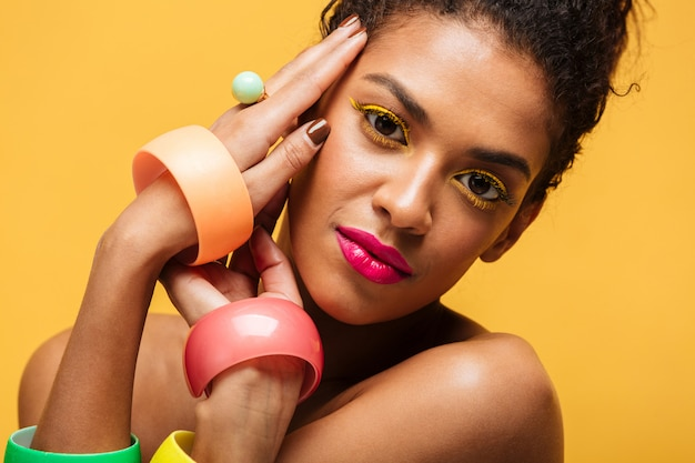 Closeup retrato de adorável mulata com pálpebras amarelas e lábios cor de rosa, olhando para a câmera de mãos dadas no rosto, isolado sobre a parede Foto gratuita