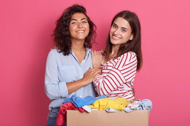 Closeup retrato de duas garotas animadas com uma caixa de papelão cheia de roupas para uso secundário Foto Premium