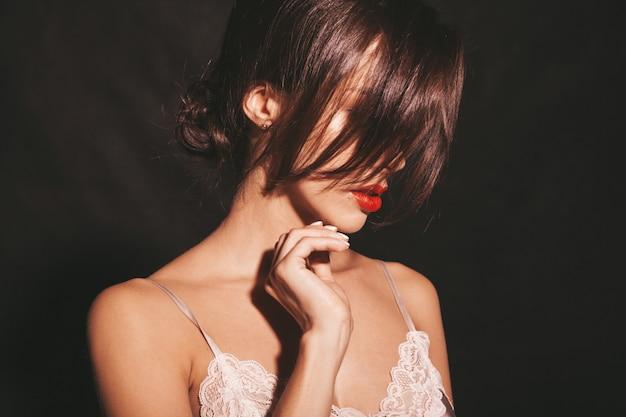 Closeup retrato de linda mulher morena sensual. garota com roupas clássicas bege elegantes. modelo com os lábios vermelhos isolados no preto Foto gratuita