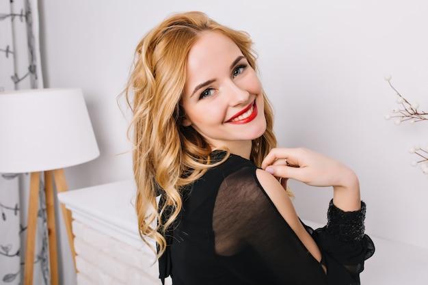 Closeup retrato de menina bonita com cabelo loiro ondulado, sorrindo, posando em um quarto branco moderno. vista lateral. usando um vestido preto elegante, blusa. Foto gratuita