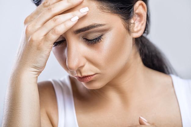 Closeup retrato de menina doente bonita sofrendo de dor de cabeça Foto Premium