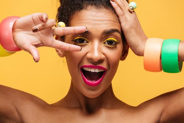 Closeup retrato de mulata brincalhão com pálpebras amarelas e lábios cor de rosa, gesticulando dois dedos no olho e olhando na câmera, isolada Foto gratuita