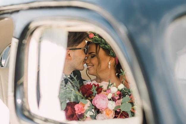 Closeup retrato de um casal apaixonado de homem e mulher no dia do casamento em um carro. a noiva e o noivo beijam. Foto Premium