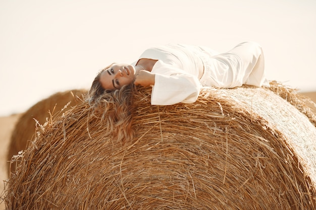 Closeup retrato de uma bela mulher sorridente. a loira em um fardo de feno. um campo de trigo ao fundo. Foto gratuita