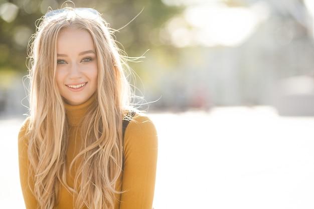 Closeup retrato de uma jovem mulher atraente ao ar livre com espaço de cópia. modelo linda loira. ladyin alegre primavera, outono, outono. Foto Premium