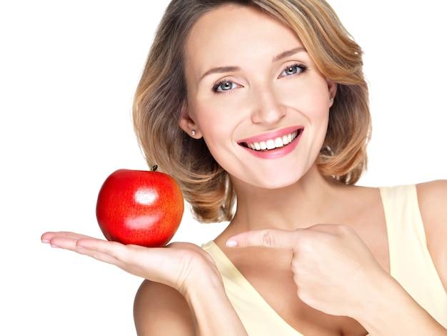 Closeup retrato de uma jovem mulher bonita e sorridente apontando o dedo para a maçã isolada no branco. Foto gratuita