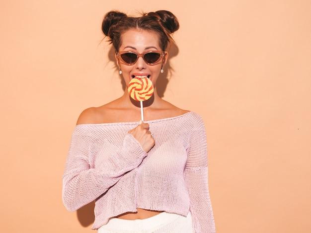 Closeup retrato de uma jovem mulher bonita sexy sorridente com penteado ghoul. menina na moda em roupas de verão casual em óculos de sol. modelo quente isolado em bege. comendo, mordendo pirulito doce Foto gratuita