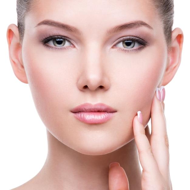 Closeup retrato do belo rosto saudável da jovem mulher muito branca com pele fresca - isolada no branco. Foto gratuita