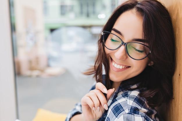 Closeup retrato inteligente jovem morena de óculos escuros, relaxando na janela. local de trabalho confortável, clima alegre, sorrindo com os olhos fechados. Foto gratuita