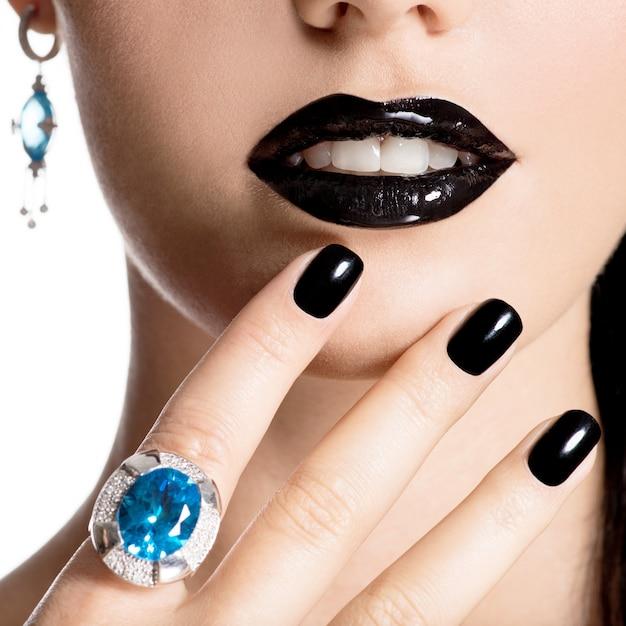 Closeup rosto de uma jovem mulher bonita com manicure preta e maquiagem brilhante de moda Foto gratuita