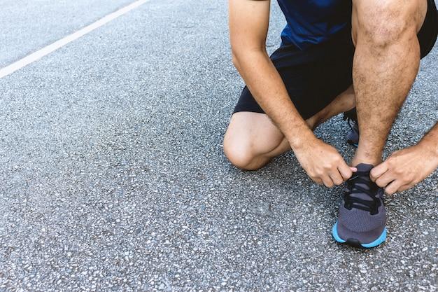 Closeup sportman amarrando o tênis Foto Premium
