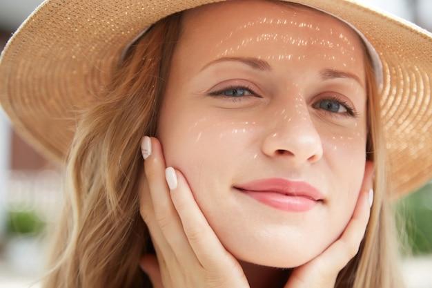 Closeup tiro da jovem mulher caucasiana em um chapéu de palha tocando seu rosto suavemente Foto gratuita
