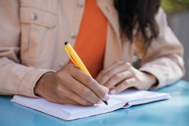 Closeup tiro da mão do aluno segurando a caneta, escrevendo no caderno, estudando, aprendendo uma língua, preparação para o exame, conceito de educação Foto Premium