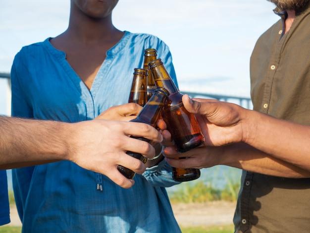 Closeup tiro de amigos tilintar de garrafas de cerveja. grupo de jovens relaxantes depois do trabalho. conceito celebração Foto gratuita