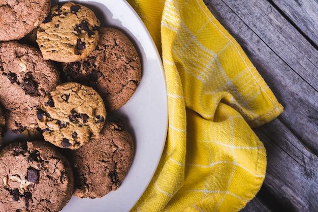 Closeup tiro de biscoitos de chocolate recém-assados em um prato branco sobre um tecido amarelo Foto gratuita