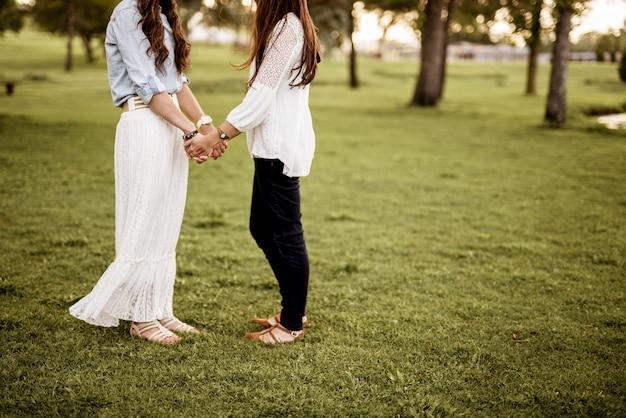 Closeup tiro de duas fêmeas de mãos dadas em pé em um campo gramado com turva Foto gratuita