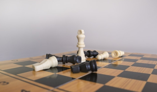 Closeup tiro de estatuetas de xadrez em um tabuleiro de xadrez com um fundo branco borrado Foto gratuita