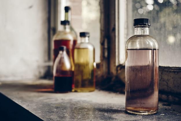 Closeup tiro de garrafas de vidro cheias de líquidos transparentes desconhecidos Foto gratuita