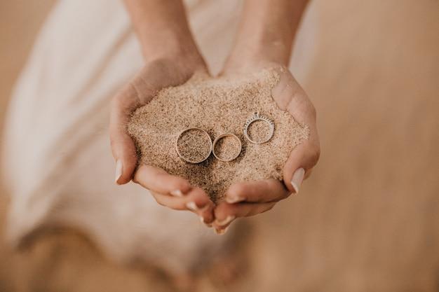 Closeup tiro de mãos femininas segurando areia com três anéis na parte superior Foto gratuita