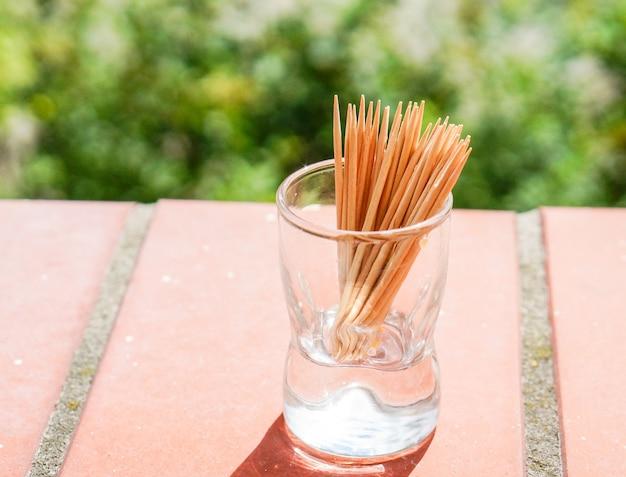 Closeup tiro de palitos de dente de madeira em um copo pequeno Foto gratuita