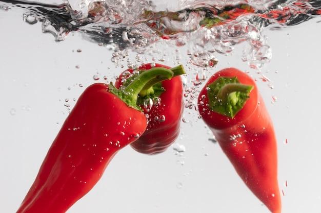 Closeup tiro de três pimentas tabasco vermelhas na água Foto gratuita