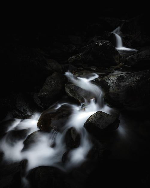Closeup tiro de um belo rio pequeno correndo através de rochas e detritos em uma floresta Foto gratuita