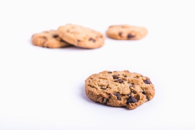 Closeup tiro de um biscoito de chocolate com biscoitos em um fundo branco desfocado Foto gratuita