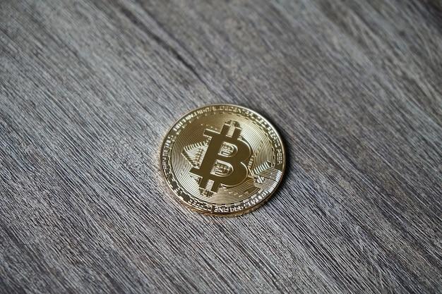 Closeup tiro de um bitcoin em uma mesa de madeira Foto gratuita