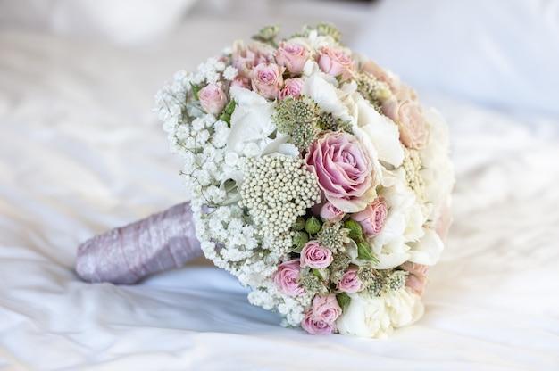 Closeup tiro de um buquê de noiva em um lençol branco com as cores branca, rosa e verde Foto gratuita
