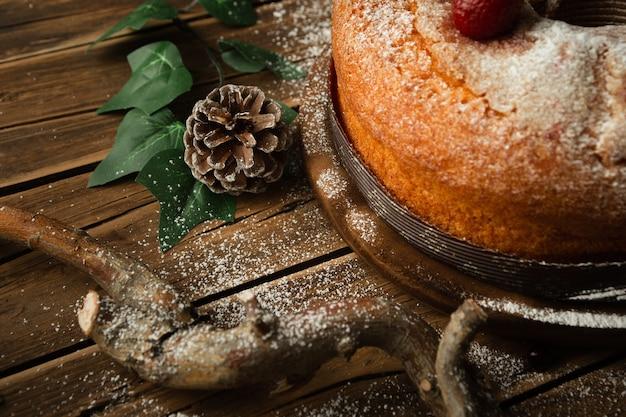 Closeup tiro de um delicioso bolo de esponja com morangos, uma pinha e amoras vermelhas na mesa Foto gratuita