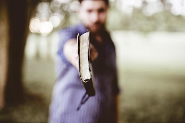 Closeup tiro de um homem segurando a bíblia em direção à câmera Foto gratuita