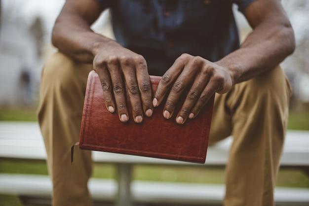 Closeup tiro de um homem sentado no parque, segurando a bíblia Foto gratuita