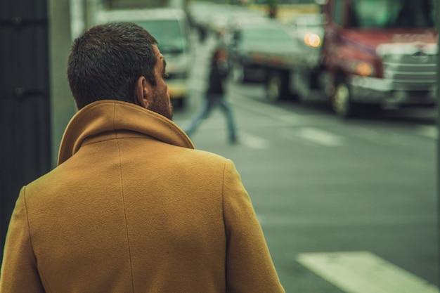 Closeup tiro de um homem vestindo casaco marrom brilhante em pé perto da rua Foto gratuita