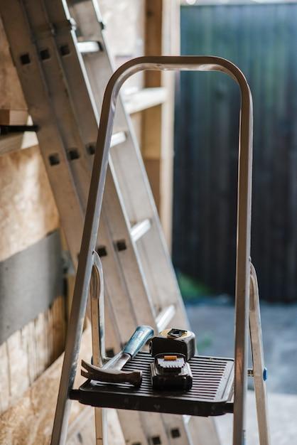 Closeup tiro de um hummer e ferramentas na escada durante a construção da casa Foto gratuita