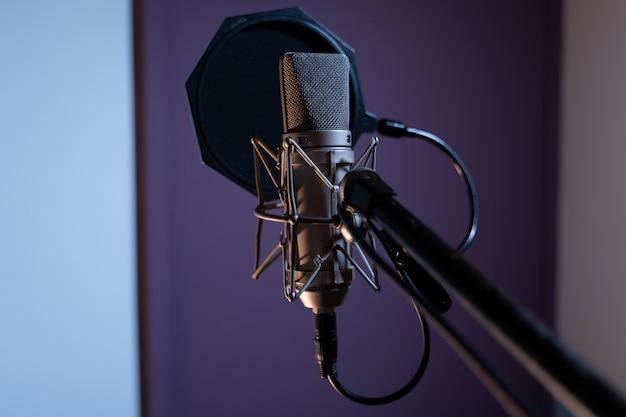 Closeup tiro de um microfone condensador com um filtro pop e uma turva Foto gratuita