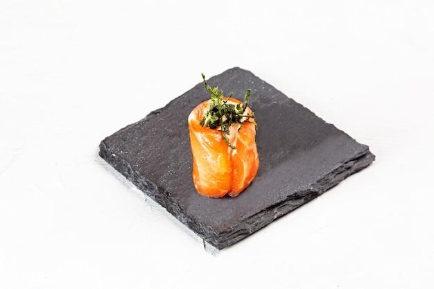 Closeup tiro de um sushi roll em uma placa de pedra preta Foto gratuita