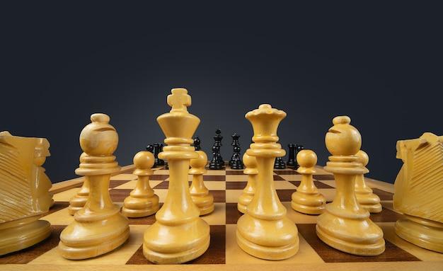 Closeup tiro de um tabuleiro de xadrez feito de peças marrons e pretas Foto gratuita