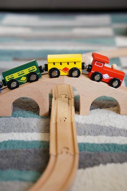 Closeup tiro de um trem de brinquedo em uma ponte de madeira Foto gratuita