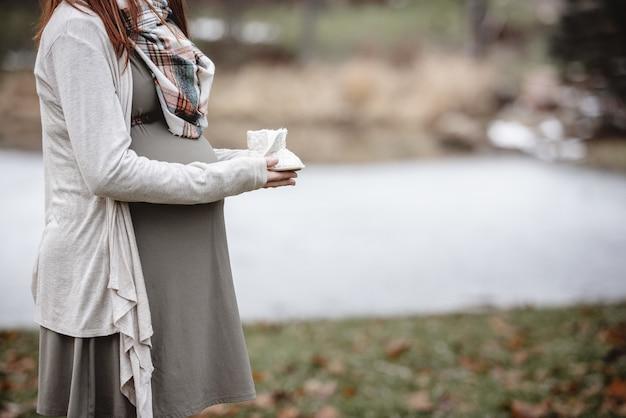 Closeup tiro de uma mulher grávida segurando sapatos de bebê Foto gratuita